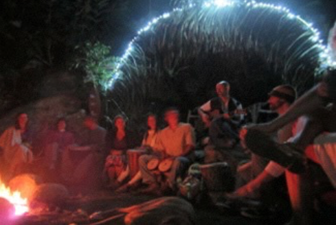Flight School participants gathered around a fire, singing together and playing various acoustic instruments.