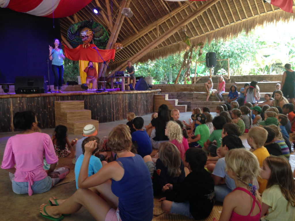 Lisa G Littlebird performing an outdoor concert in front of an audience of mostly children.