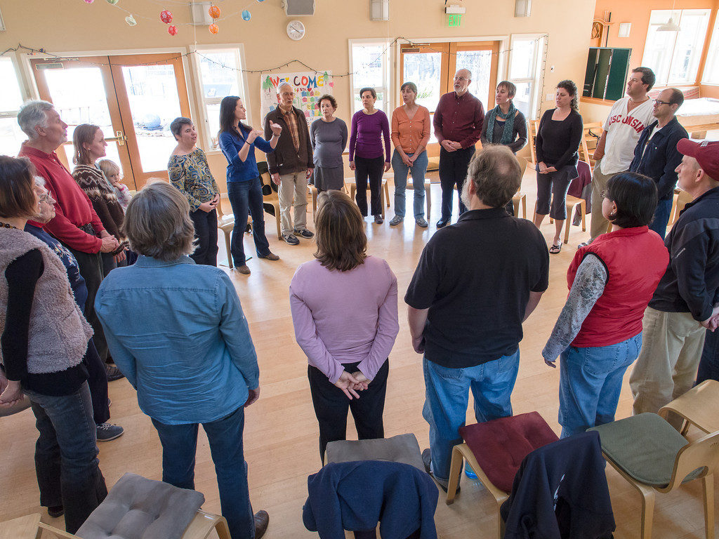 A group of song leaders gathered at the Flight School in a circle - they are singing together.